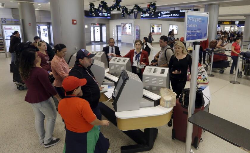 Un grupo de viajeros hacen fila para viajar en el Aeropuerto Internacional de Miami el 25 de noviembre del 2014. (AP Photo/Alan Diaz)