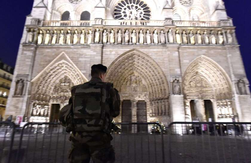 A French serviceman stands guard outside the Notre Dame Cathedral as people queue to attend a church serviceon Dec.25 in Paris.