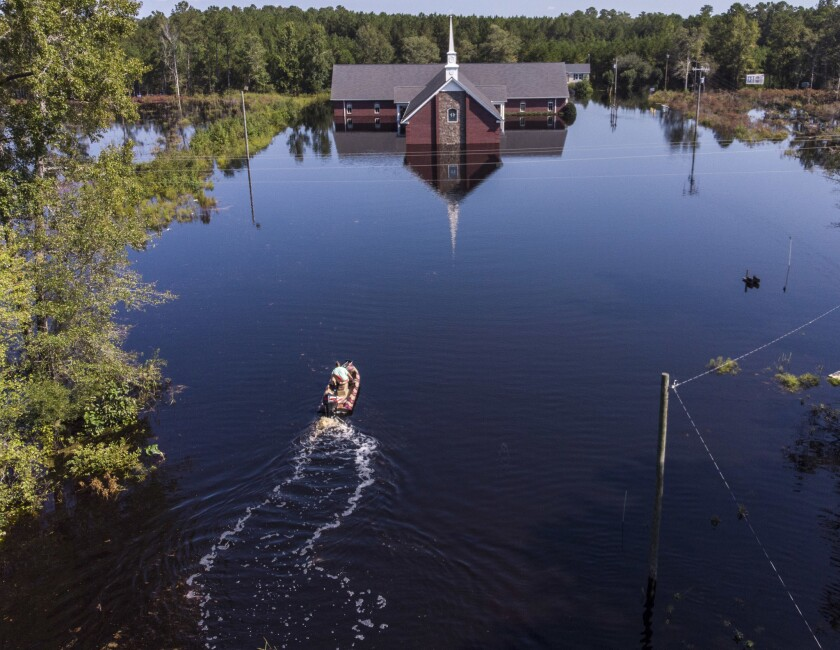 Avery Singleton takes a boat to Pine Grove Baptist Church Saturday, Sept. 22, 2018, in Brittons Neck