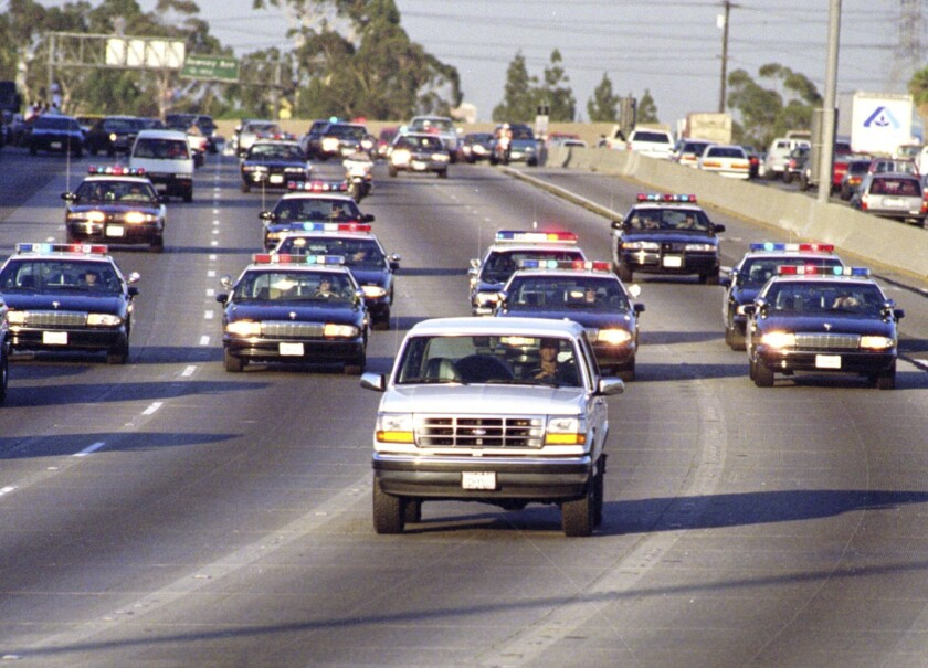 California Highway Patrol units chase Al Cowlings, who is driving the white Bronco, and O.J. Simpson, hiding in the rear, on the 91 Freeway shortly after Simpson was charged in slayings.