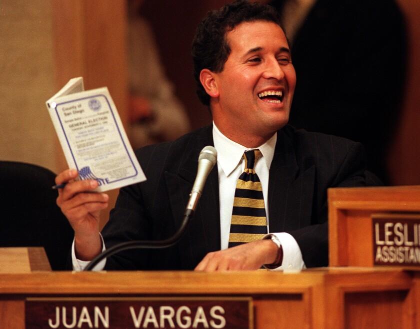 """مردی پشت میز با علامت نشسته است """"یوان وارگاس"""""""