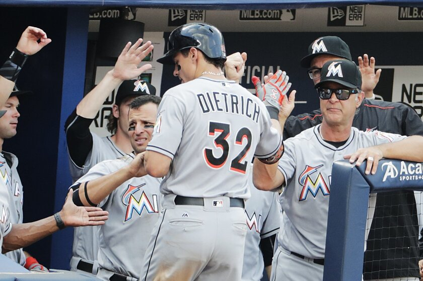 Miami Marlins' Derek Dietrich is high-fived by manager Don Mattingly, right, and teammates after hitting a two-run home run to score Justin Bour in the sixth inning of a baseball game against the Atlanta Braves, Sunday, May 29, 2016, in Atlanta. (AP Photo/David Goldman)