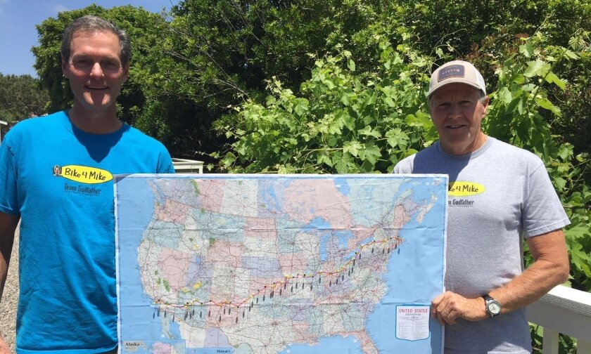 Jim Quigley (left) and Kevin McCauley hold a map previewing their cross-country bike trek. They're riding to fundraise for Team Godfather Charitable Foundation.