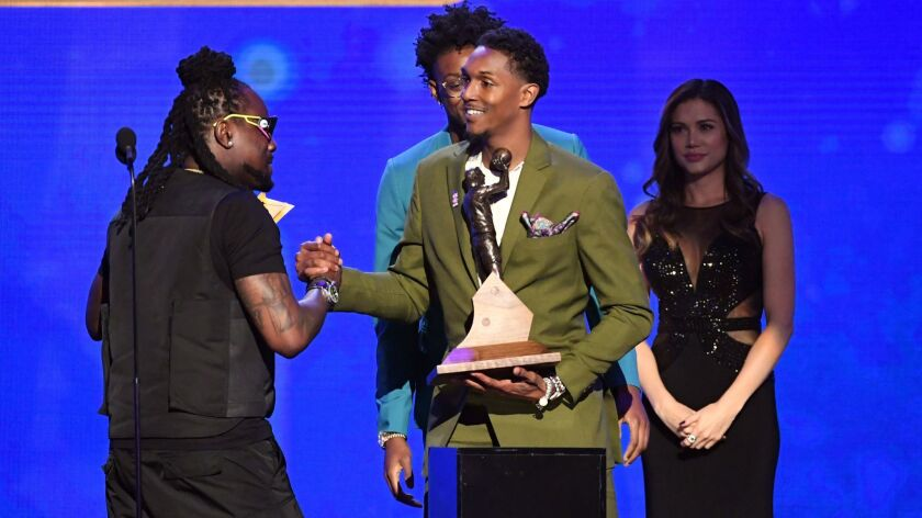 Lou Williams accepts the NBA Sixth Man of the Year award from rapper Wale on stage during the NBA Awards at Barker Hangar on June 24, 2019, in Santa Monica.