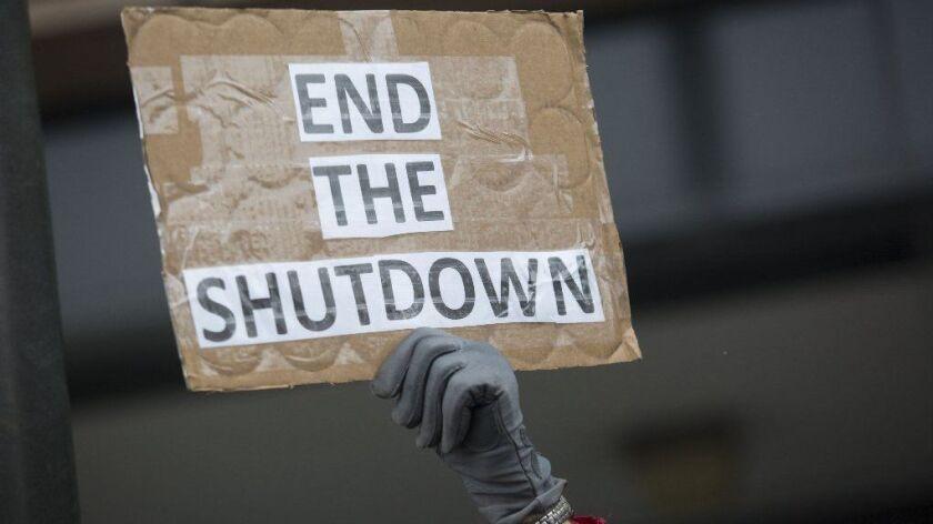 A demonstrator holds a sign protesting the government shutdown at the James V. Hansen Federal Building in Ogden, Utah, on Jan. 10.