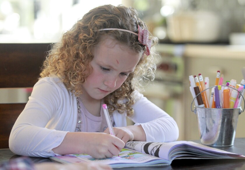 Nina Jensen, 5, works on a pre-kindergarten activity book at home in San Diego on March 19, 2020.