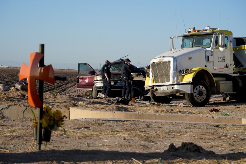 Holtville, CA - March 02: On Tuesday, March 2, 2021 in Holtville, CA., law enforcement investigator look over the SUV after tow wreckers separated it from the large tractor trailer. The accident was the scene of a deadly crash on State Highway115 near the U.S.-Mexico border. The crash Tuesday morning left at least 13 people dead and several others injured. (Nelvin C. Cepeda / The San Diego Union-Tribune)