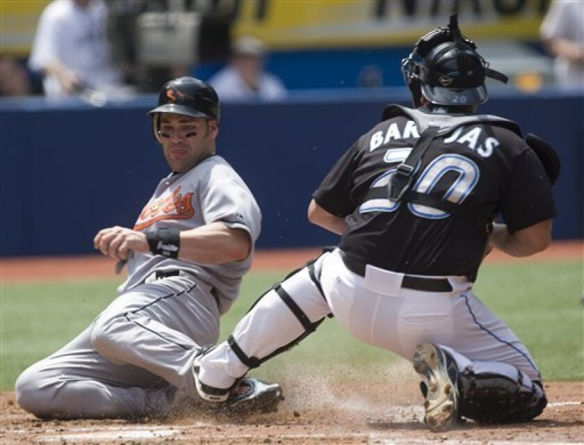 Toronto Blue Jays catcher Rod Barajas fails to tag Baltimore Orioles' Luke Scott as he slides safely into home on a hit from Jay Payton in fifth inning of a baseball game in Toronto, Saturday June 7, 2008. (AP Photo/The Canadian Press, Adrian Wyld)