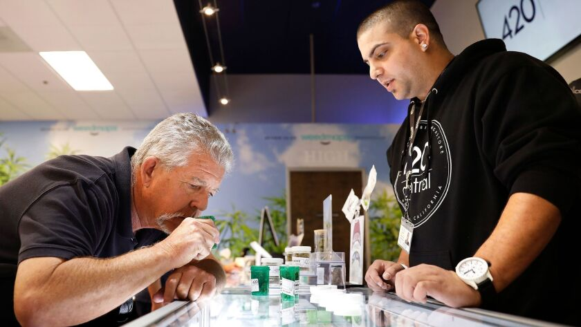Craig Burns shops for marijuana for recreational use with the help of budtender Jake Walcher, right, at 420 Central, a dispensary in Santa Ana, Calif. on Jan. 4.