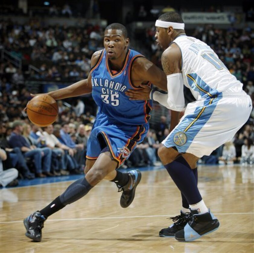 Oklahoma City Thunder forward Kevin Durant, left, works the ball inside past Denver Nuggets forward Carmelo Anthony in the first quarter of an NBA basketball game in Denver on Wednesday, March 3, 2010. (AP Photo/David Zalubowski)