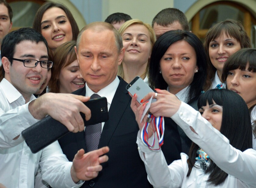 Russian President Vladimir Putin poses for photos with call center operators after his nearly four-hour exchange with Russians on live television Thursday.