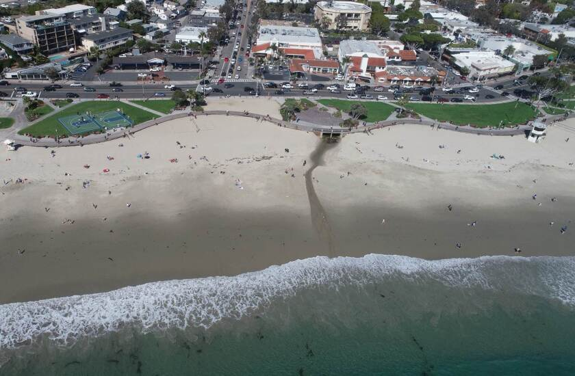 An aerial photo taken of Main Beach around 3 p.m. March 21, 2020, shows people in the water and relaxing on the sand despite the governor's order to stay home.