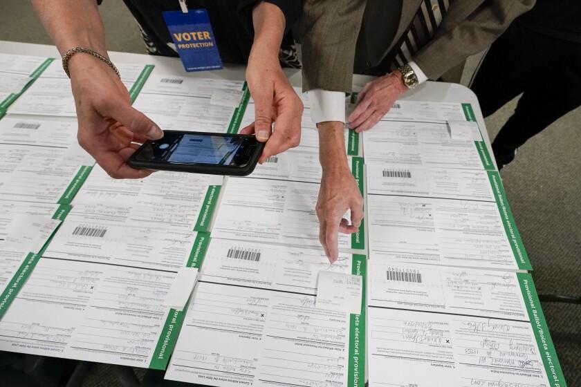 ARCHIVO - En esta fotografía de archivo del 6 de noviembre de 2020, un supervisor de escrutinio fotografía papeletas provisionales en el condado Lehigh mientras prosigue el conteo de votos de la elección general en Allentown, Pensilvania. (AP Foto/Mary Altaffer, Archivo)