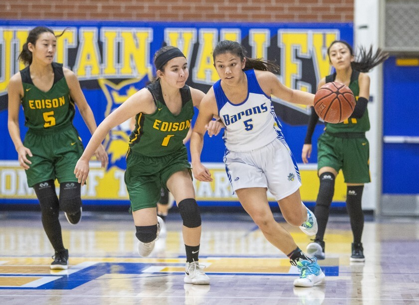 Fountain Valley's Kat Luu, right, dribbles the ball against Edison's Noelle Duffey in a Sunset Conference crossover game.