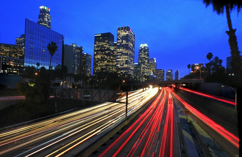 The glare of head and brake lights line the 110 Freeway during the evening rush hour. Faced with growing shortfalls in highway funding, California officials are trying to determine if a mileage fee would be more effective at raising revenue for road projects than the state gas tax.