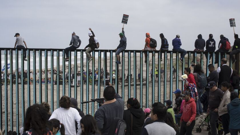 Central American migrants traveling with a caravan gather at the border wall, some sitting on top of