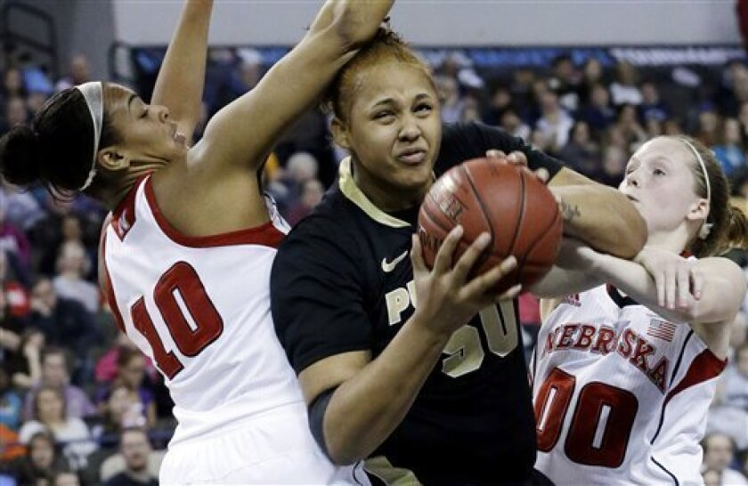 Purdue forward Taylor Manuel, center, drives to the basket against Nebraska forward Meghin Williams, left, and guard Lindsey Moore during the first half of an NCAA college basketball game in the Big Ten Conference tournament in Hoffman Estates, Ill., on Saturday, March 9, 2013. (AP Photo/Nam Y. Huh