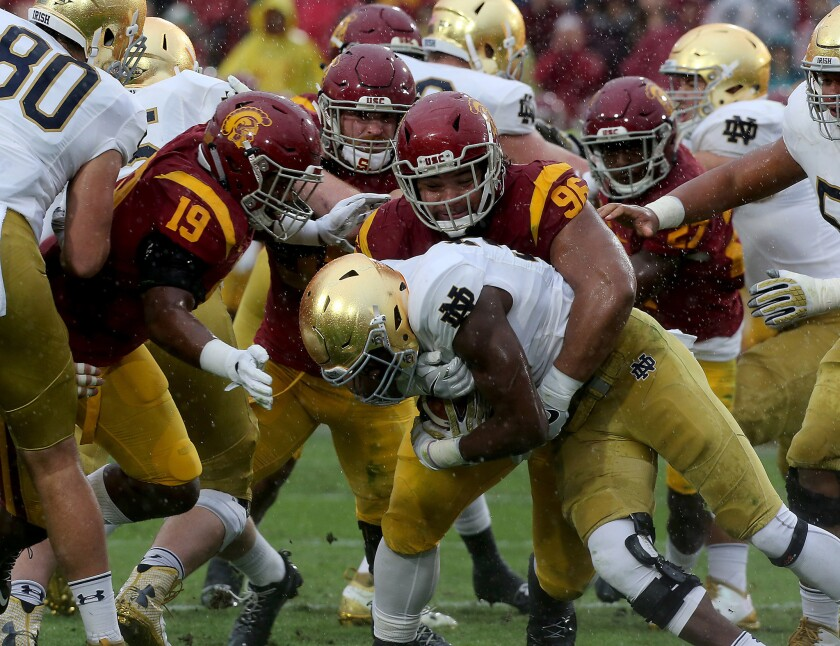 USC nose tackle Stevie Tu'ikolovatu wraps up Notre Dame running back Josh Adams in the second quarter.