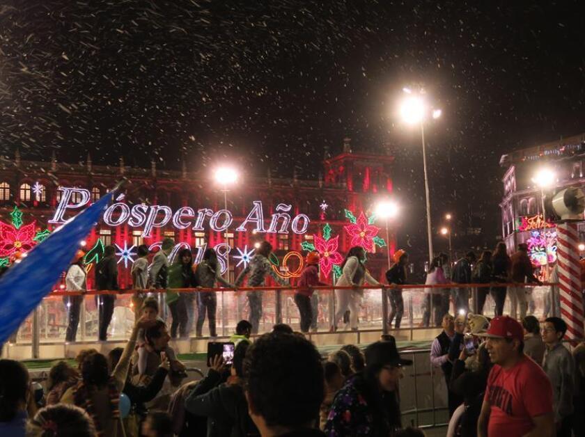 Asistentes patinan en una pista de hielo mientras una máquina simula lanzar nieve este sábado, 23 de diciembre de 2017, en Ciudad de México (México). El Zócalo de la Ciudad de México, lugar histórico y emblemático para la historia del país, se transforma durante Navidad en una gigante pista de hielo en la que diariamente hacen equilibrios miles de mexicanos. EFE