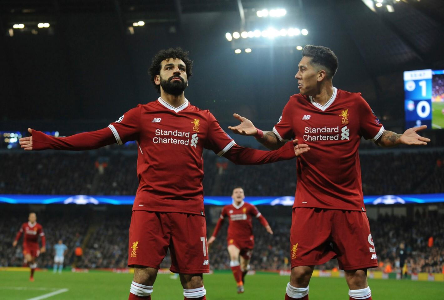 Mohamed Salah (izquierda) del Liverpool festeja tras anotar el primer gol de su equipo junto a Roberto Firmino en el partido contra Manchester City en los cuartos de final de la Liga de Campeones, en Manchester, el martes 10 de abril de 2018.
