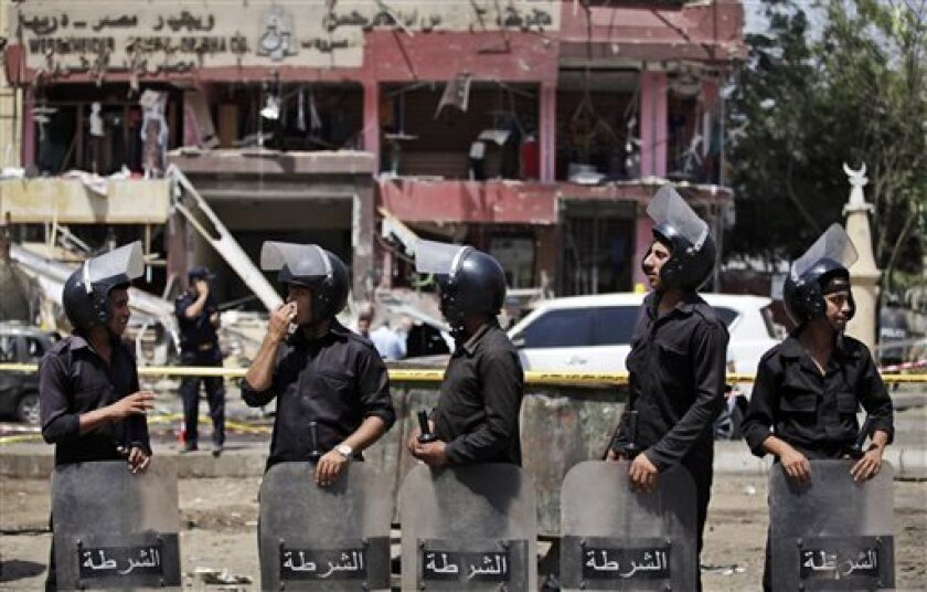 """Egyptian security officers guard the scene of a bomb attack targeting the convoy of Egypt's Interior Minister Mohammed Ibrahim, in Nasr City, Cairo, Egypt, Thursday, Sept. 5, 2013. A """"large"""" explosive targeted the convoy of Egypt's interior minister Thursday in Cairo's eastern Nasr City district, the first attack on a senior government official since a coup toppled the country's Islamist president July 3, 2013. (AP Photo/Khalil Hamra)"""