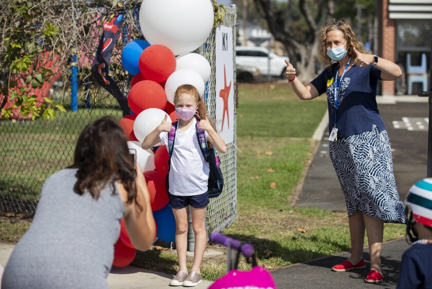 Danielle Hodge, left, takes a picture of her daughter, Isla, 6, and her first-grade teacher, Shari Gaeta.