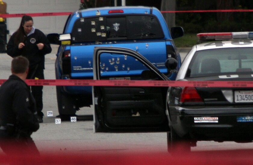 Police investigators examine a blue pickup truck riddled with bullets on Redbeam Avenue in Torrance. LAPD officers, thinking that shooting suspect Christopher Dorner might have been in the vehicle, unleashed a fusillade, wounding a woman and her mother.