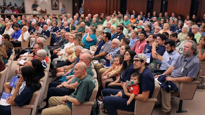 A crowd for and against the proposed development project for the old Escondido Country Club site crowds the Escondido Planning Commission meeting. Many people for it wore blue and against it wore gr