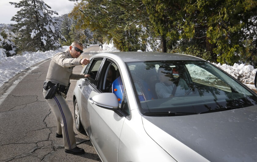 California High Patrol Officer Juan Escobar directs the driver of a car traveling along Canfield Road on Palomar Mountain to pull over so he can help them properly secure the car seat their toddler was riding in on Saturday.