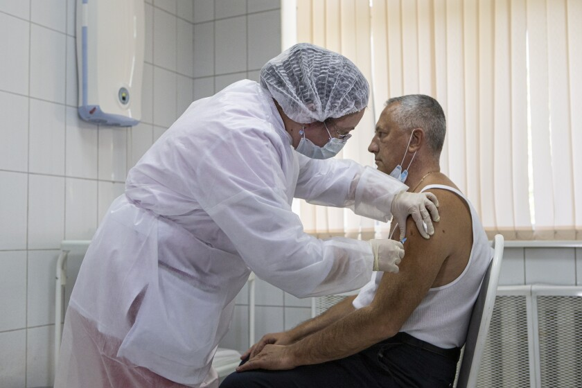 Russian medical worker administers a shot of Russia's experimental COVID-19 vaccine in Moscow.