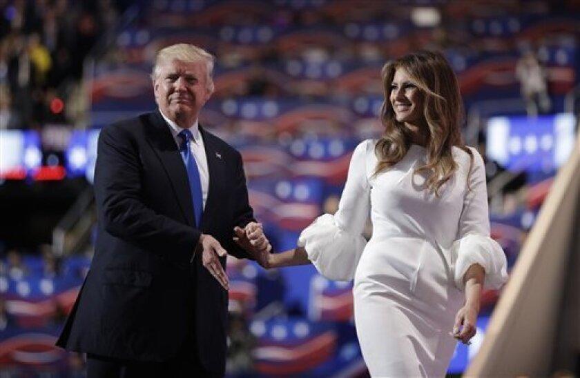 El candidato presidencial republicano Donald Trump acompaña en el escenario a su esposa Melania durante la Convención Nacional Republicana, el lunes 18 de julio de 2016, en Cleveland, Ohio. (AP Foto/John Locher)