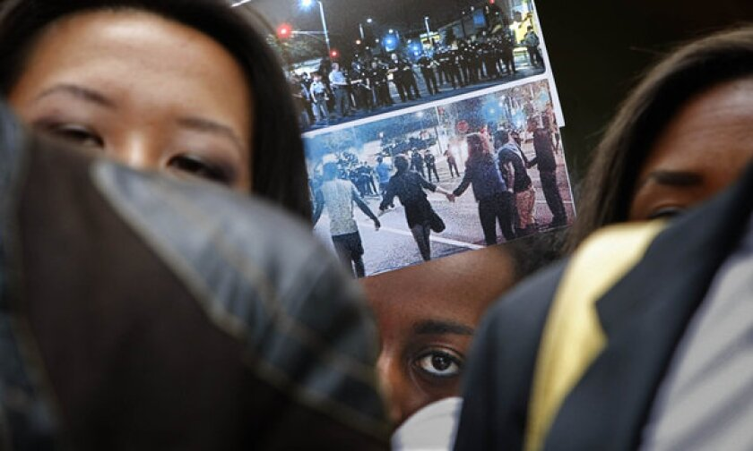 During a protest at USC, a student holds up photographs of the LAPD response to a party Saturday night.