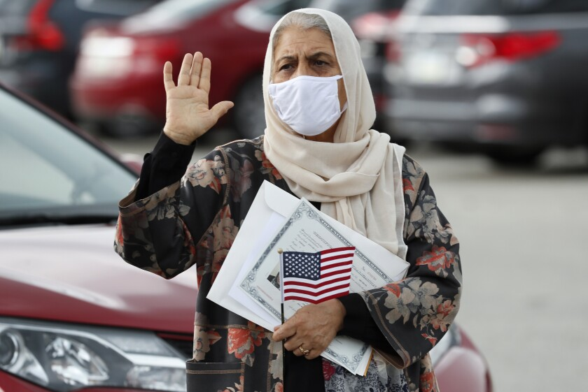 FILE - In this June 26, 2020, file photo, Aisha Kazman Kammawie, of Ankeny, Iowa, takes the oath of allegiance during a drive-thru naturalization ceremony at Principal Park in Des Moines, Iowa. U.S. Citizenship and Immigration Services has transformed under President Donald Trump to emphasize fraud detection, enforcement and vetting, which has delayed processing and contributed to severe fiscal problems. Its revamp came as the administration sought to cut legal immigration by making it more dependent on employment skills and wealth tests. (AP Photo/Charlie Neibergall, File)