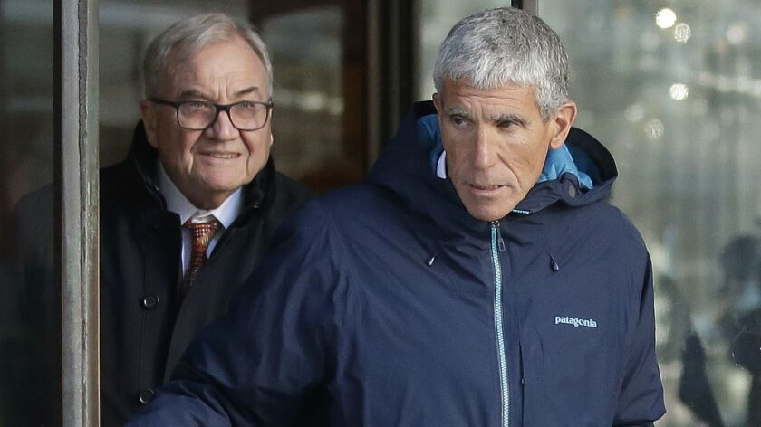 """William """"Rick"""" Singer (front) exits federal court in Boston on Tuesday after he pleaded guilty to charges in a nationwide college admissions bribery scandal."""