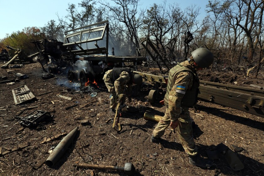 Ukrainian soldiers outside Mariupol sort through the wreckage of their artillery convoy, which was destroyed by Russian shelling.