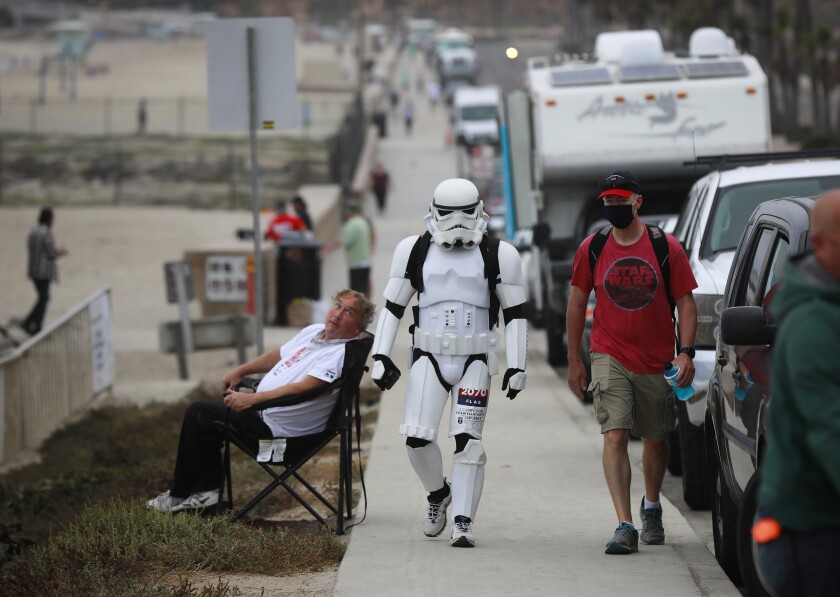 """Jeffry Priela, 38, of Carlsbad, walks down Highway 101 Sunday during a fundraisin """"ruck"""" in his Star Wars stormtrooper armor."""