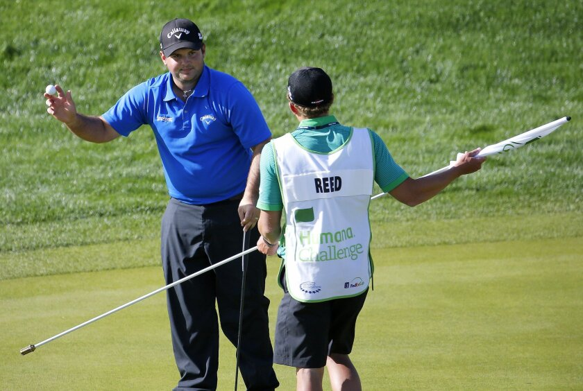 Patrick Reed looks to his caddie after making his birdie putt on the ninth green during the third round of the Humana Challenge PGA golf tournament on the Nicklaus Private course at PGA West, Saturday, Jan. 18, 2014, in La Quinta, Calif. Reed shot a 9-under par for the third day in a row and is 27-