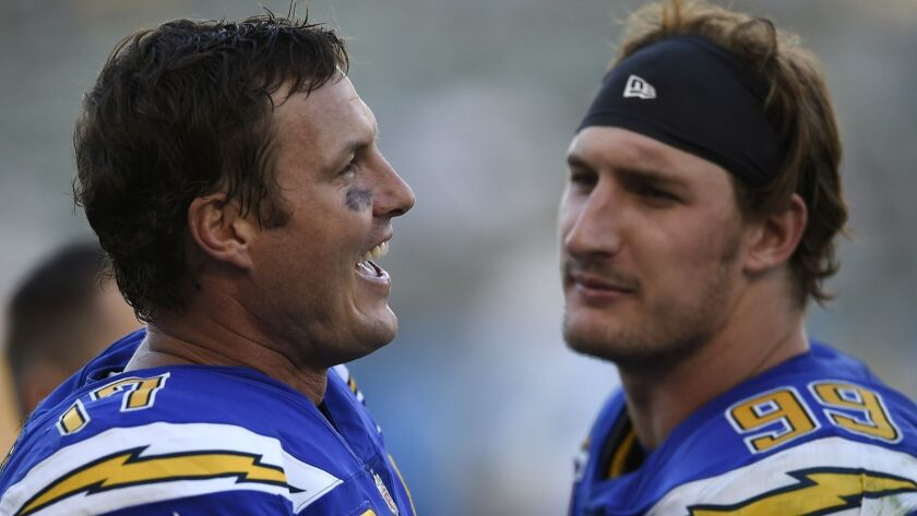 Los Angeles Chargers quarterback Philip Rivers, left, talks to teammate Joey Bosa during the second
