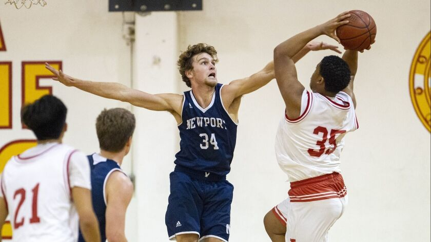 Newport Harbor's Dayne Chalmers attempts to block a shot from Loara's Cade Flowers during the Grizzl