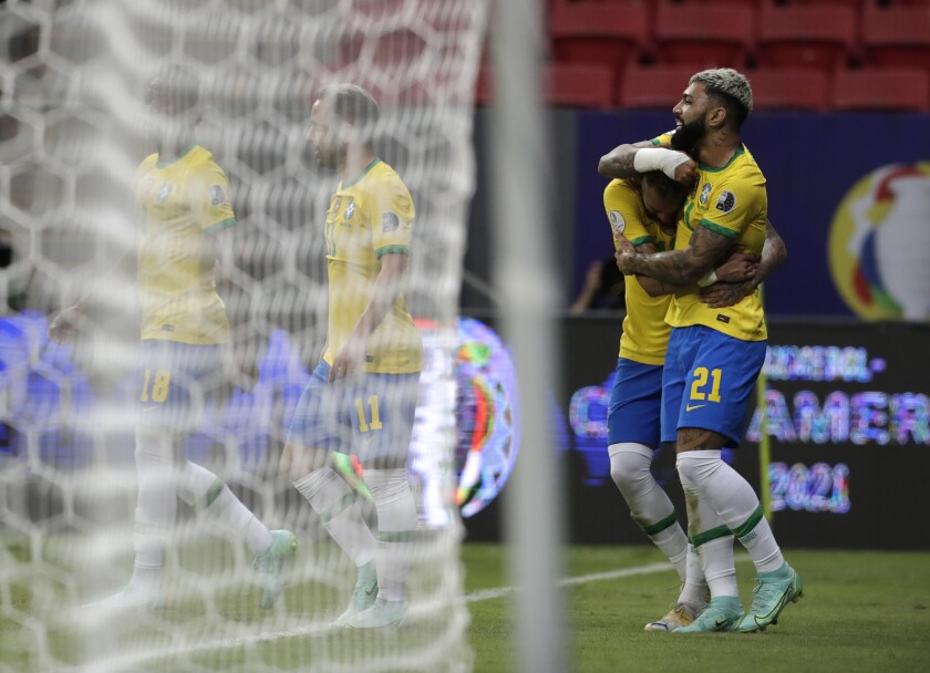Brazil's Gabriel Barbosa, right, celebrates scoring his side's third goal against Venezuela with teammate Neymar during a Copa America soccer match at the National Stadium in Brasilia, Brazil, Sunday, June 13, 2021. (AP Photo/Eraldo Peres)