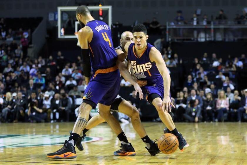 El jugador de Suns Devin Booker (d) conduce el balón ante la marca de Manu Ginobili (c) de Spurs, hoy sábado 14 de enero de 2017, durante un partido de temporada regular de la NBA en la Arena Ciudad de México. EFE