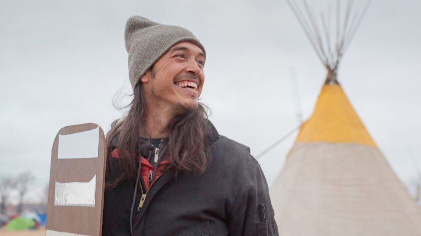 Artist Cannupa Hanska Luger holds one of his mirrored shields at the Oceti Sakowin Camp in Standing Rock, N.D.