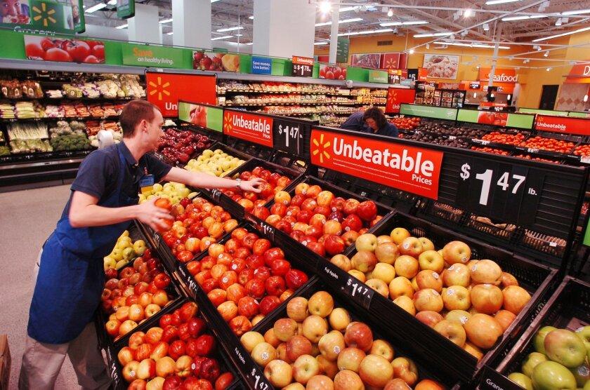 A Walmart associate stocks produce.