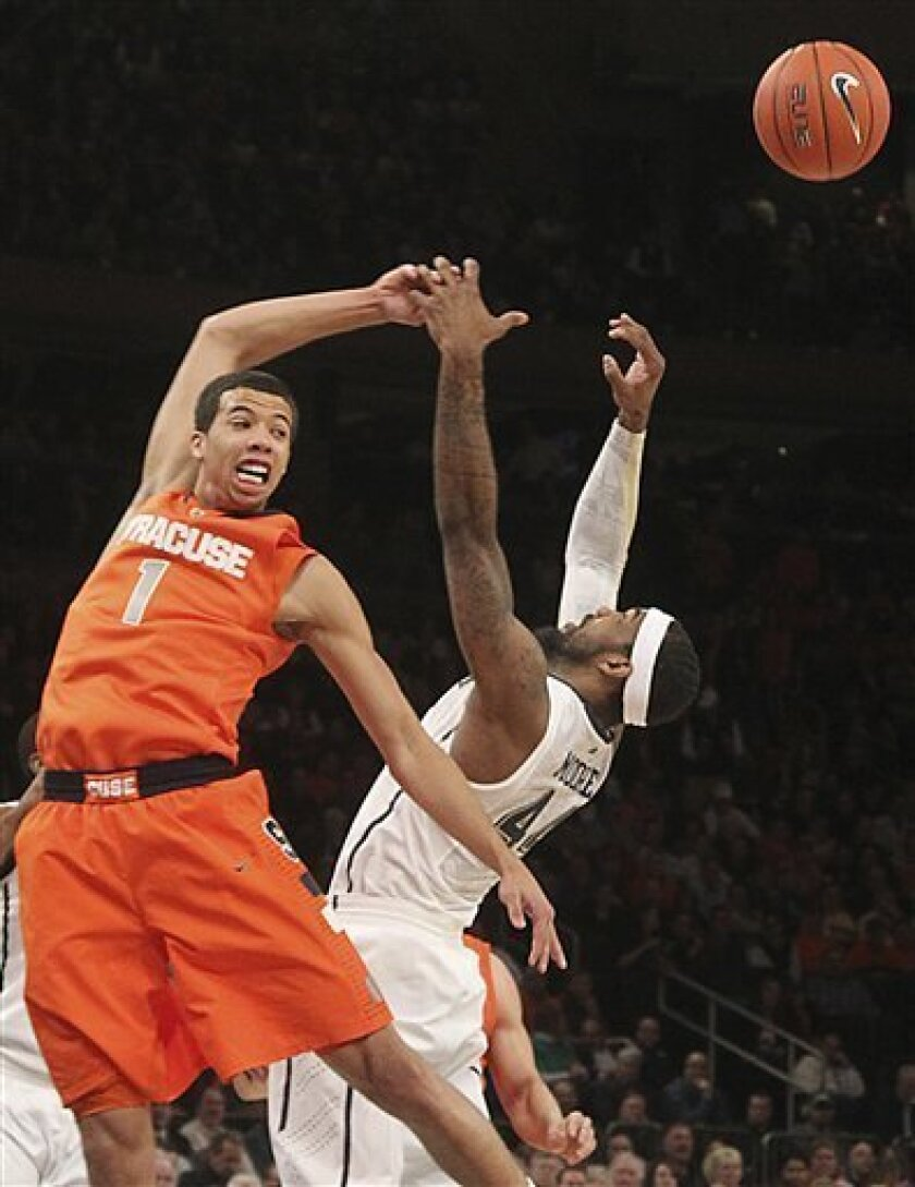 Syracuse's Michael Carter-Williams, left, and Pittsburgh's J.J. Moore fight for a rebound during the first half of an NCAA college basketball game at the Big East Conference tournament, Thursday, March 14, 2013 in New York. (AP Photo/Mary Altaffer)