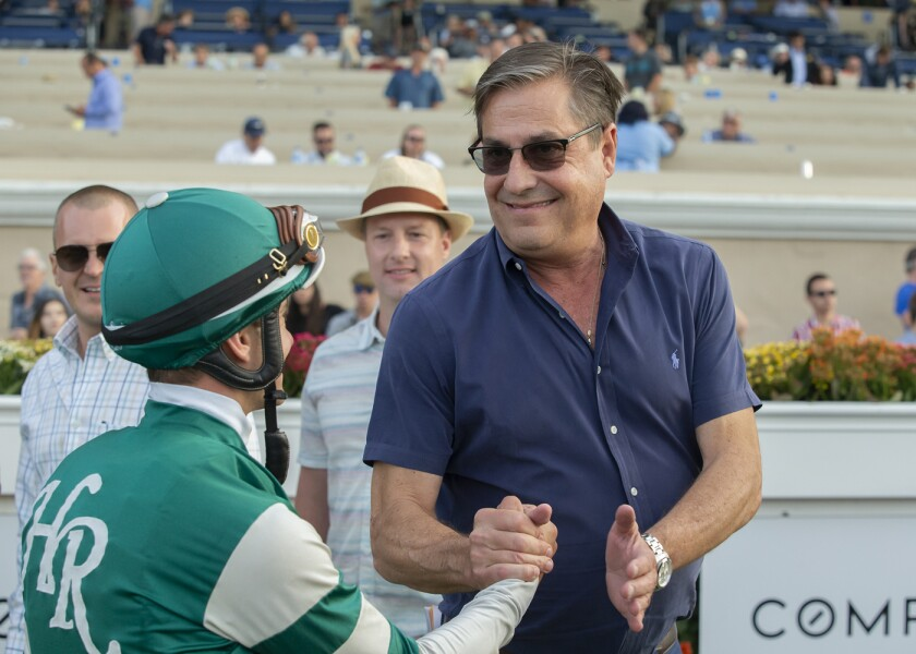 Trainer John Sadler, right, celebrates with jockey Flavien Prat, left, after Higher Power's victory in the Grade I, $1,000,000 Pacific Classic horse race on Saturday at Del Mar Thoroughbred Club.