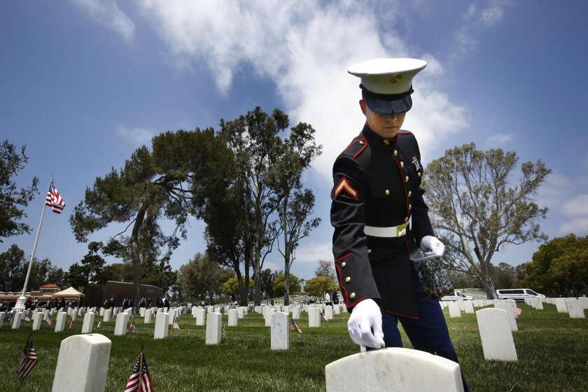 Marine Pfc. Morgan Weibel places a penny for the fallen at a Memorial Day celebration at the Los Angeles National Cemetery.