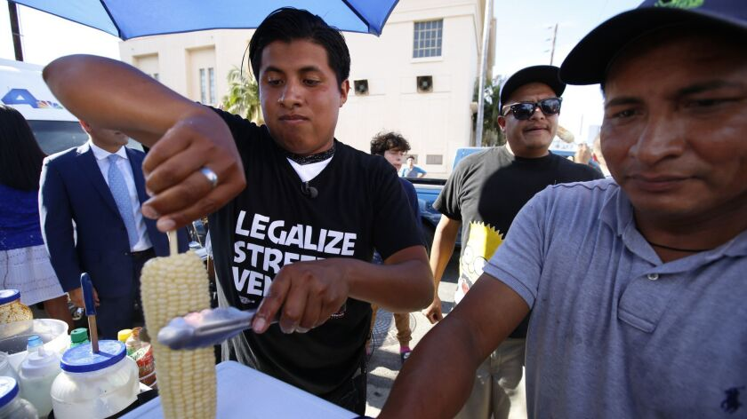 Benjamin Ramirez, left, and his father Alex Ramirez serve food from their cart during a rally in Hollywood in July 2017.