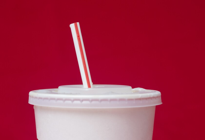 A large soft drink with a plastic straw from a McDonald's restaurant.