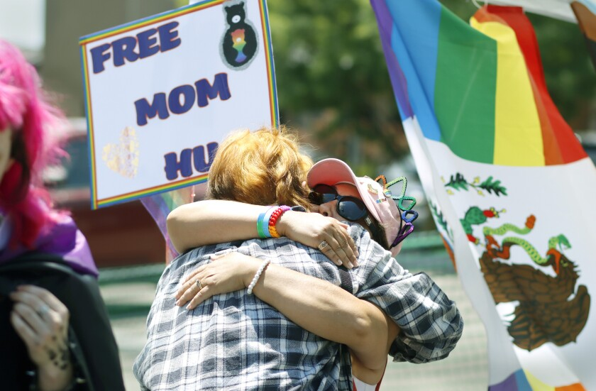 Elisa Scholes hugs a woman at She Fest on Saturday afternoon at the Free Mom Hugs booth