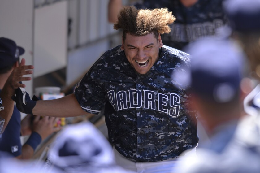 Padres' Josh Naylor is congratulated in the dugout after hitting a home run during the third inning of game against the Colorado Rockies Sunday, Aug. 11, 2019, in San Diego.